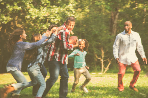 multi-ethnic family playing football in backyard at thanksgiving. - game of life stock photos and pictures