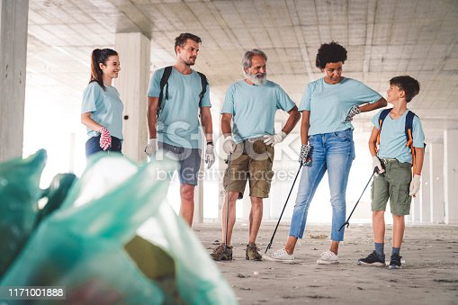 Group of ethnic diverse people, young and senior, happy community service people, volunteering to clean the environment. People picking up trash and putting into the garbage bags. Group of people cleaning the environment of waste and recycling.