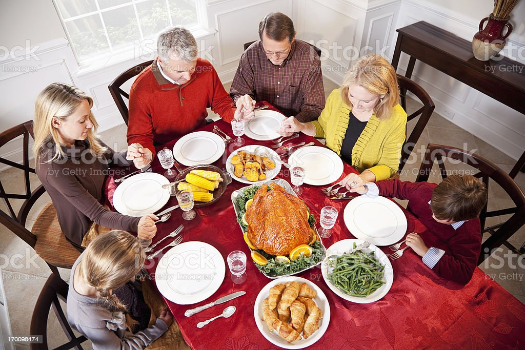 Multi-ethnic family saying prayer before holiday dinner royalty-free stock photo