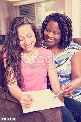 1051247474 istock photo Multi-ethnic family.  Teenage girl and mom, teacher at home studying. 538153438
