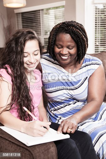 1051247474 istock photo Multi-ethnic family.  Teenage girl and mom, teacher at home studying. 538181318