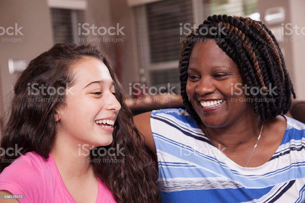Multi-ethnischen Familie. Teenager-Mädchen und die Mutter zu Hause fühlen. Umarmungen. – Foto