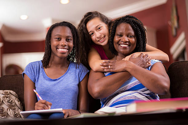 Multi-ethnic family.  Teenage girls and mom at home studying, talking. stock photo