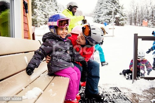 Black father with his multi daughter and son and his caucasian ethnicity wife skying during an afternoon day in a small town in Quebec Canada. It was their first time skying. They are with their caucasian friends. The color and horizontal photo was taken in Quebec Canada.