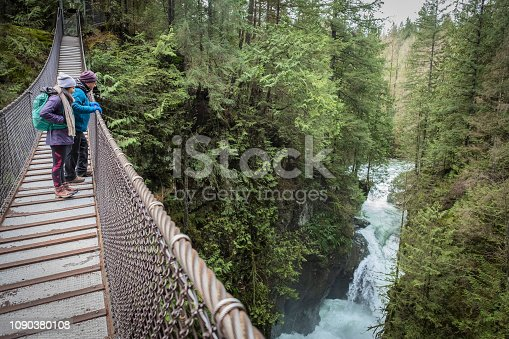 istock Multi-Ethnic Father and Daughter Viewing Canyon Waterfall from Suspension Bridge 1090380108