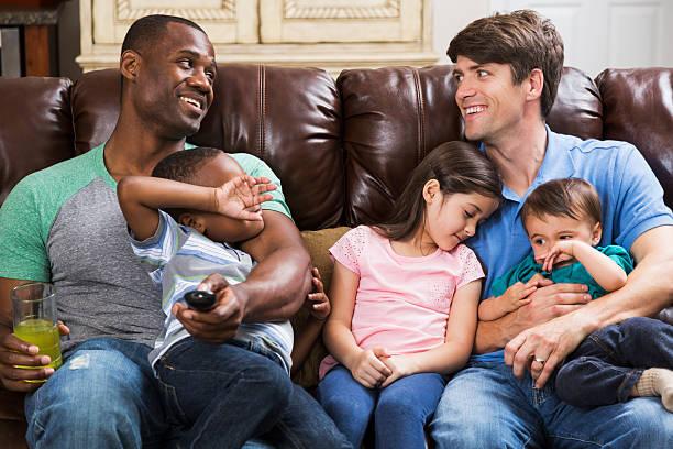 多民族の父親が子供にソファー、テレビ鑑賞 ストックフォト