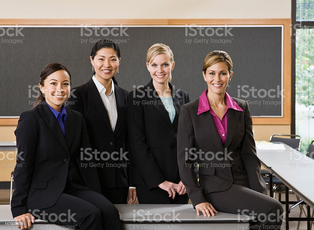 Multi-ethnic female co-workers posing in conference room royalty-free stock photo
