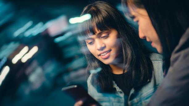 Multiethnische Freundinnen teilen sich nachts Smartphone auf der Stadtstraße. – Foto