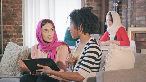 Multi-Ethnic Female Professionals Interact with Digital Tablet stock photo