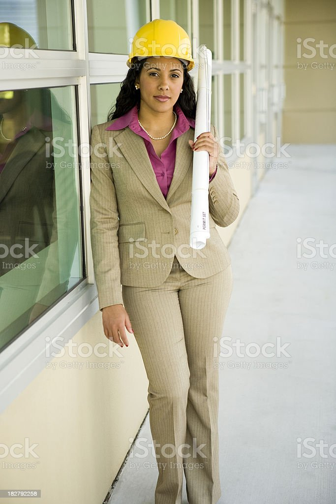 Multi-ethnic female wearing hard hat holding plans royalty-free stock photo
