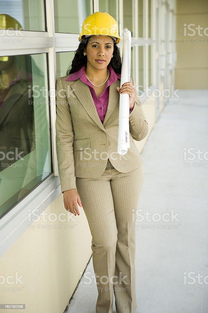 Multi-ethnic female wearing hard hat holding plans stock photo