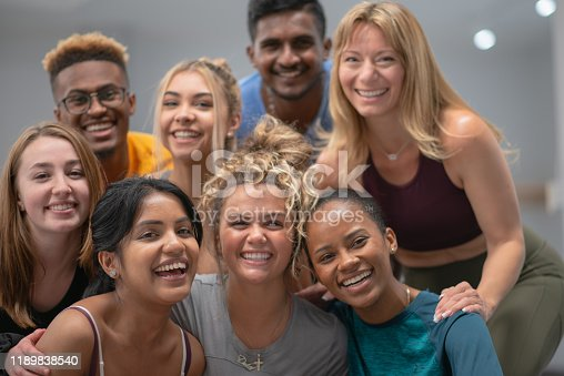 A group of ethnically diverse young adults huddle together and pause for a portrait.  They are wearing comfortable active wear and are smiling as they enjoy each others company.