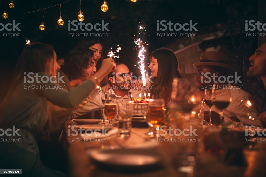 Multi-ethnic friends celebrating birthday and singing at rustic dinner party stock photo