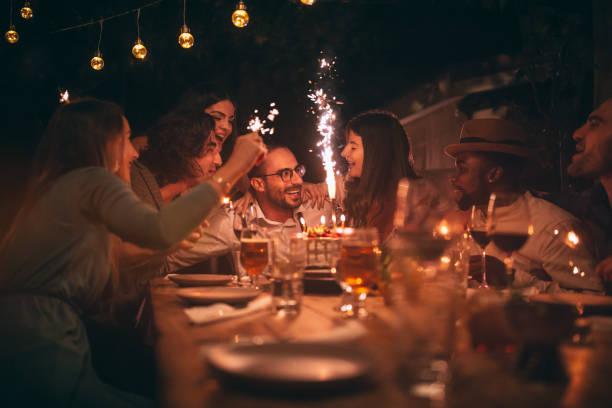 multi-ethnischen freunde geburtstag feiern und singen bei rustikalen dinner-party - französische land tisch stock-fotos und bilder