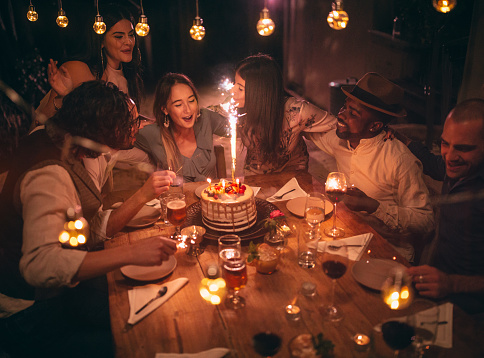 Young multi-ethnic friends celebrating birthday and singing at rustic countryside village house dinner party