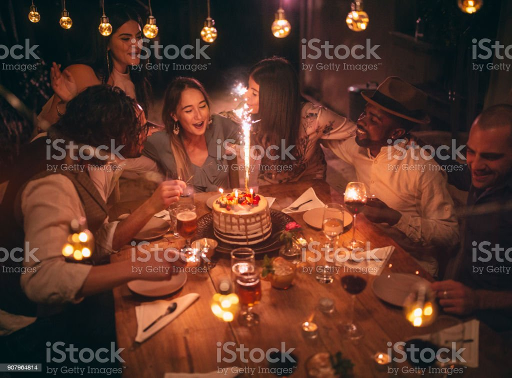Multi-ethnic friends celebrating birthday at rustic cottage dinner party stock photo