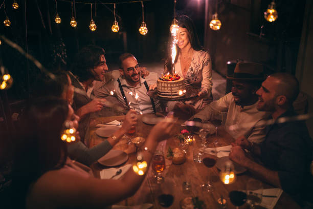 Multi-ethnic friends celebrating birthday at rustic cottage party in village stock photo