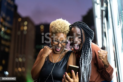 istock Multi-Ethnic Friends Celebrating Good News on Mobile 959689960