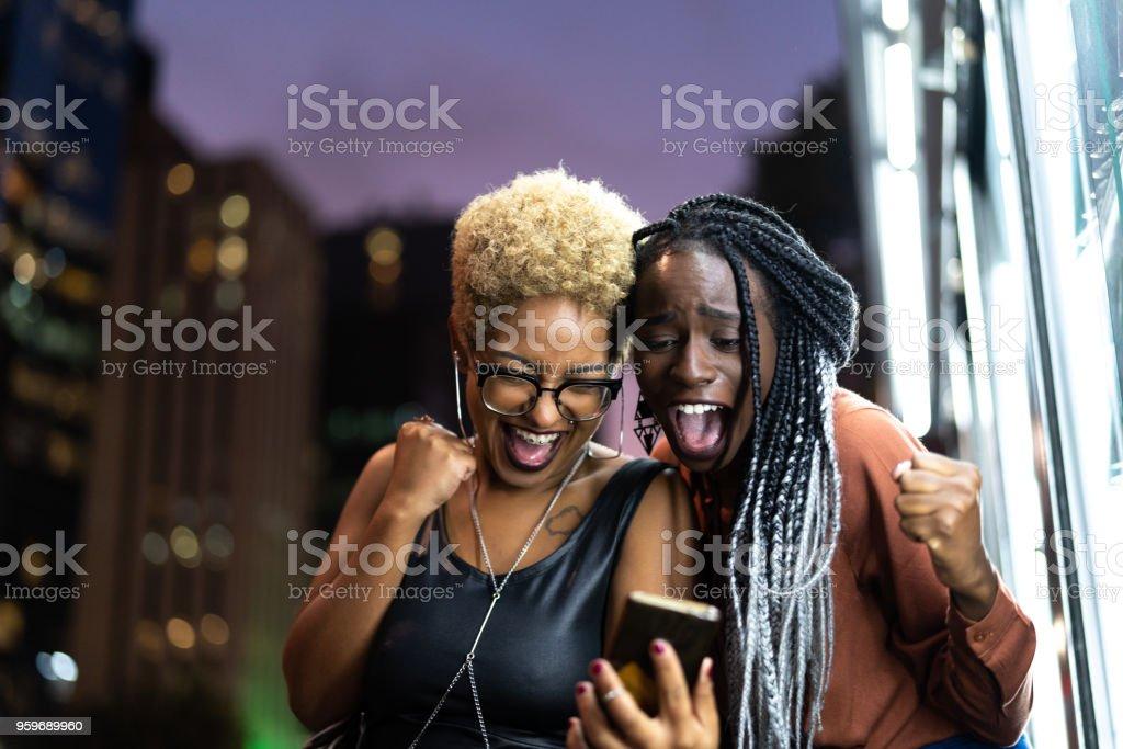 Multi-Ethnic Friends Celebrating Good News on Mobile stock photo