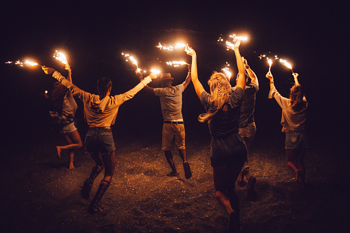 Young multi-ethnic friends celebrating Fourth of july running with sparklers on the beach at night