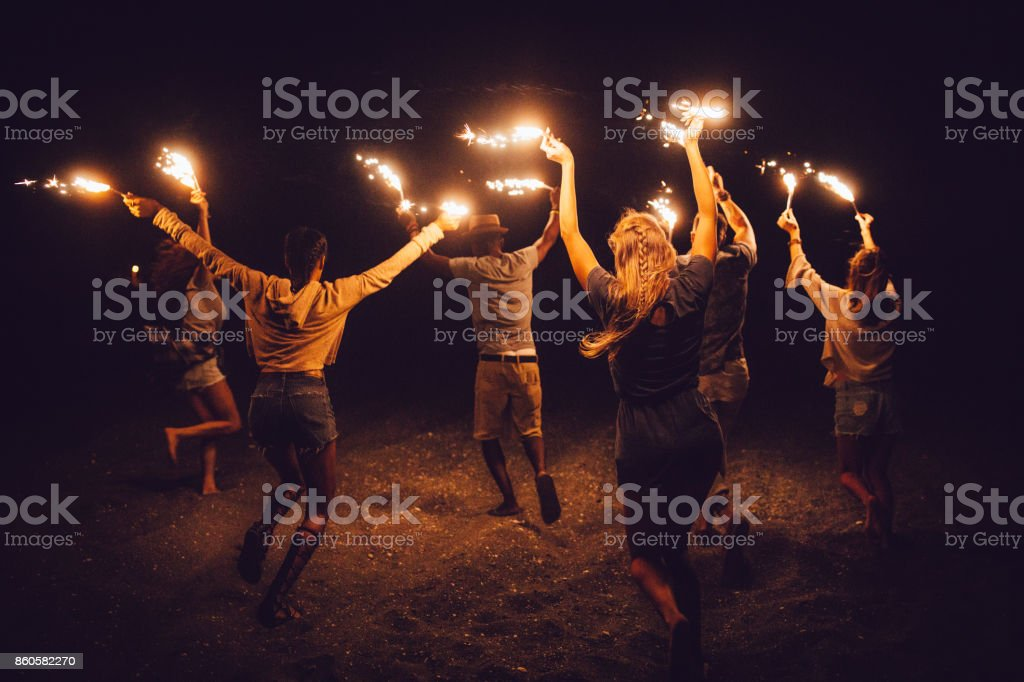Multi-ethnic friends celebrating with sparklers at night on the beach stock photo