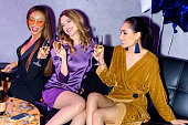 multiethnic friends clinking glasses of champagne during party