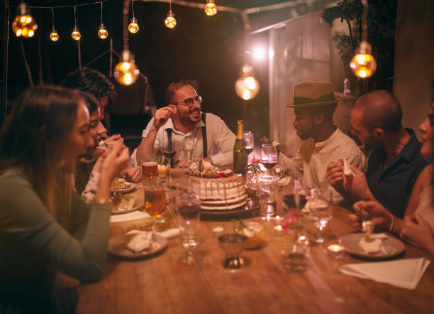 Multi-ethnic friends eating gourmet birthday cake at rustic dinner party stock photo