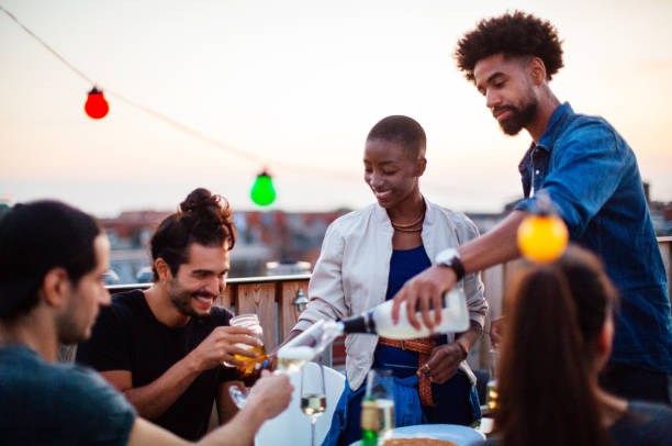 Multi-ethnic friends enjoying drinks at barbecue reunion party stock photo