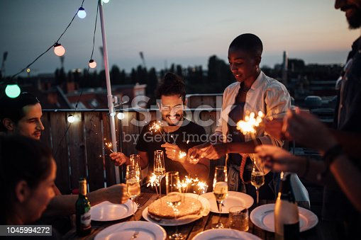Multi-ethnic friends sitting around a table with cake and sparklers in hand at rooftop party.  Men and women igniting sparklers placed on a cake during sunset.