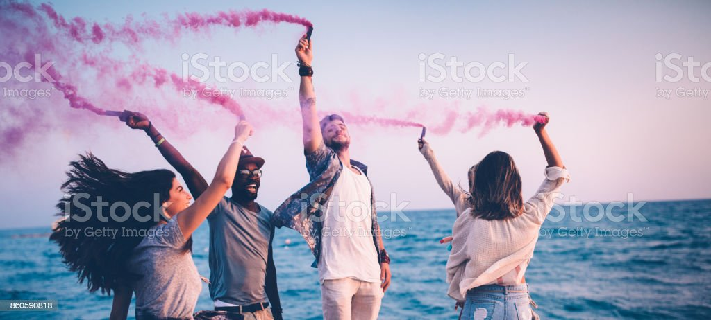 Multi-ethnic friends having fun with smoke bombs by the sea stock photo