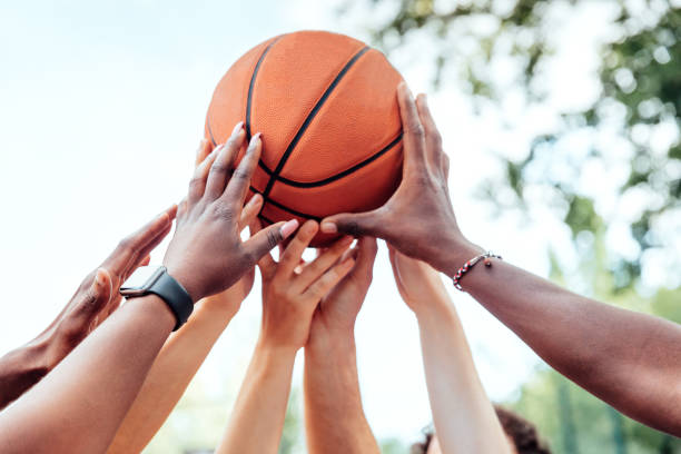 Multi-ethnic friends holding basketball stock photo