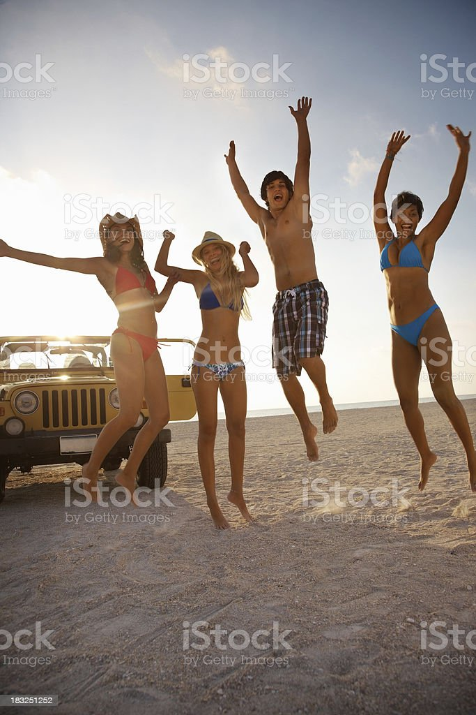 Multi-ethnic friends jumping on beach with jeep in background royalty-free stock photo