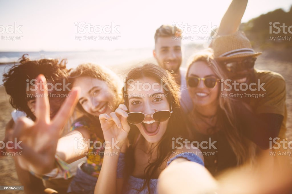 Multi-ethnic friends taking selfies at the beach on summer holidays stock photo