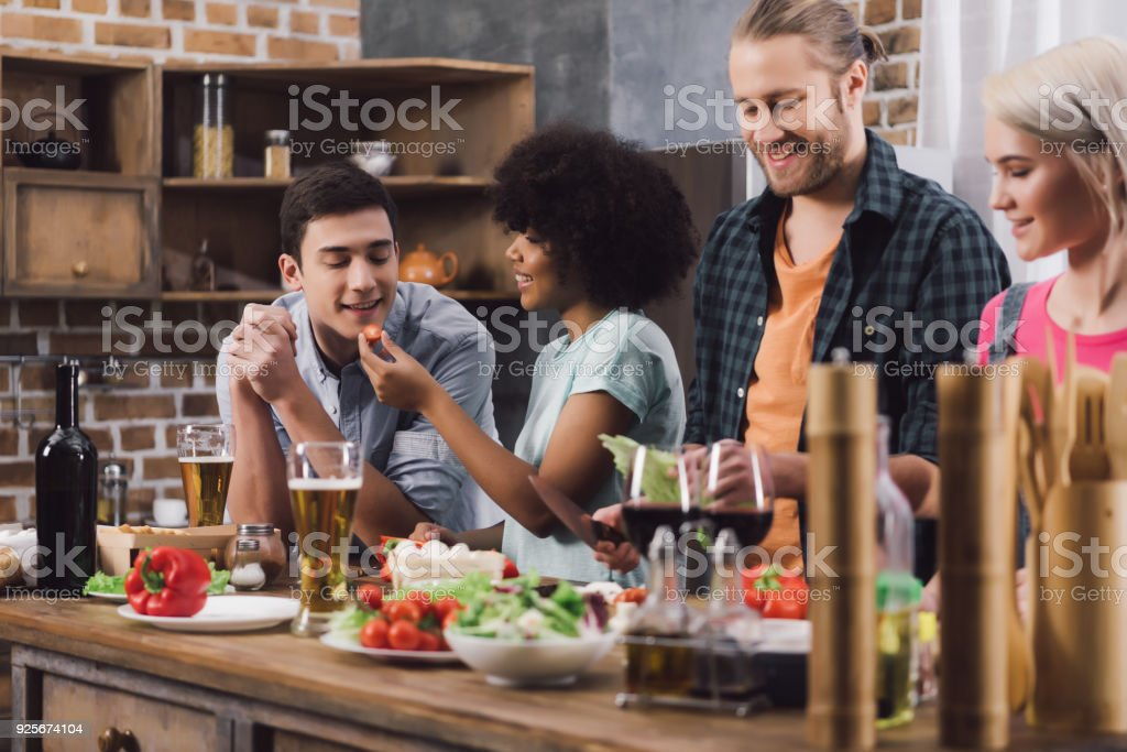 multiethnic friends tasting some food while cooking in kitchen stock photo