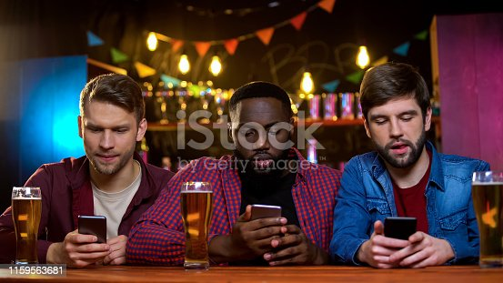 istock Multiethnic friends using smartphones sitting in pub, problem with communication 1159563681