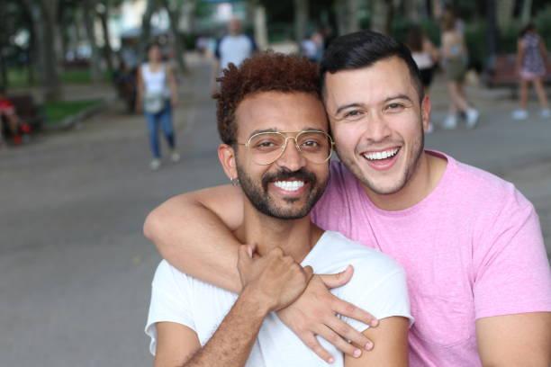 Casal gay multiétnica no parque - foto de acervo