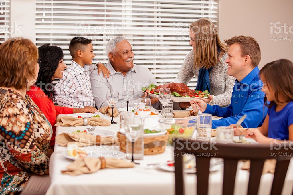 Multi-ethnic, generation family enjoys thanksgiving dinner. Hispanic, caucasian family prepares to enjoy holiday dinner together. Daughter-in-law serves turkey to family.  Dining table. Grandparents, children, grandchildren.  8-9 Years Stock Photo