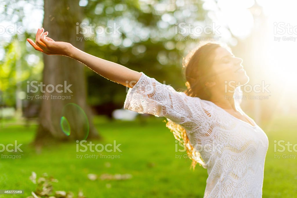 Multi-ethnic girl enjoying the warmth of a sunset stock photo