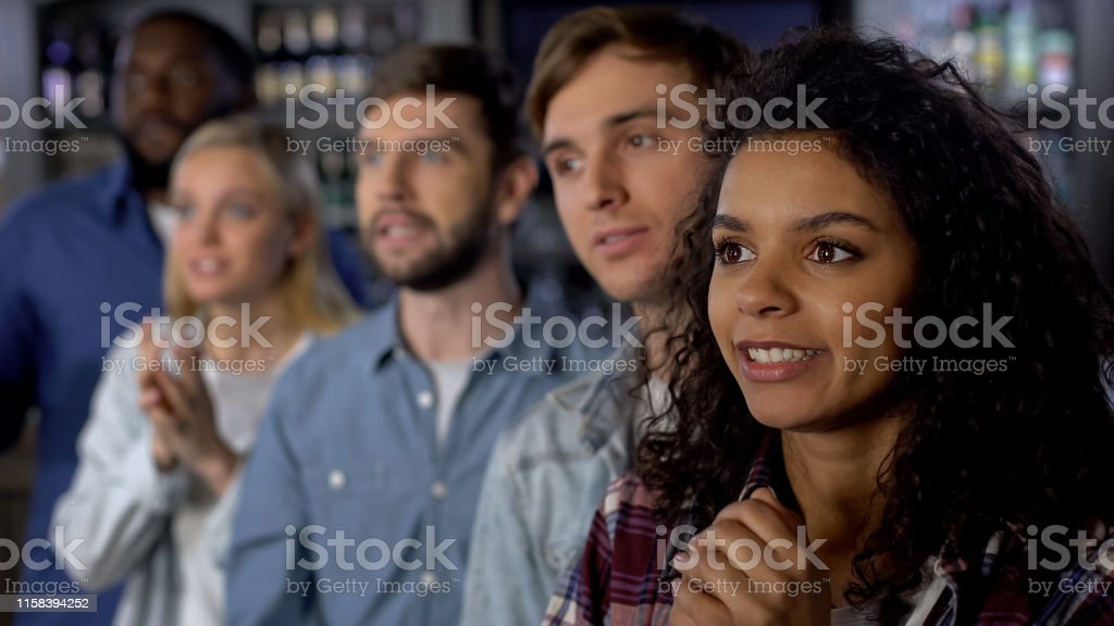 Multi-ethnic girl with friends rooting for national team, event...
