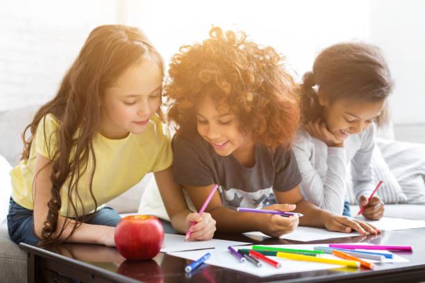 chicas multiétnicas dibujando en la mesa con lápices de colores - dibujar fotografías e imágenes de stock