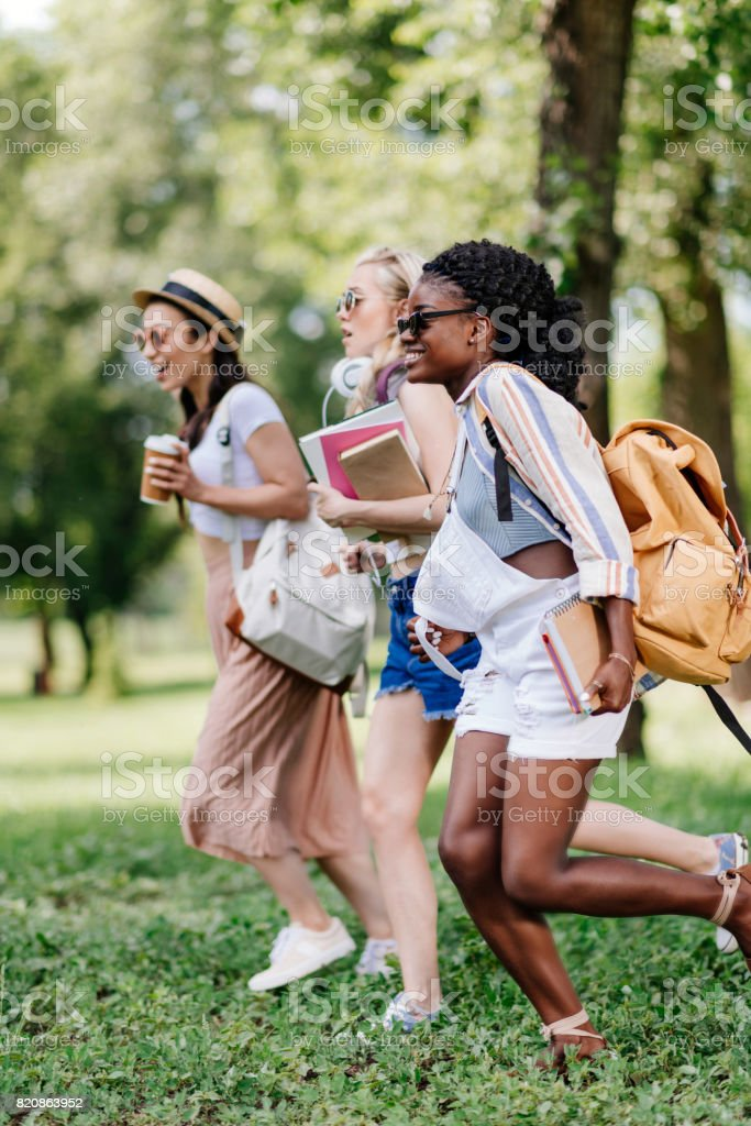 multiethnic girls in sunglasses holding books and running in park stock photo