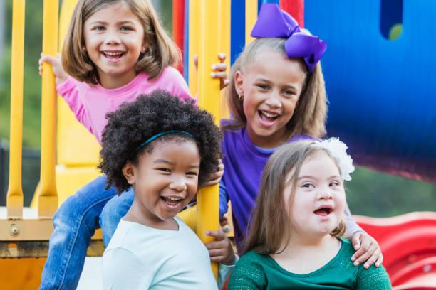 Multi-ethnic girls playing on playground stock photo