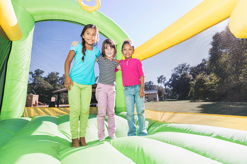 Multi-ethnic girls standing together on bounce house