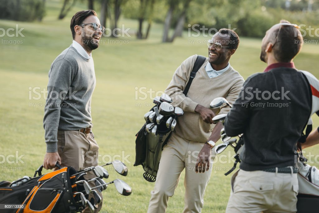 multiethnic golf players with golf clubs having fun on golf course stock photo