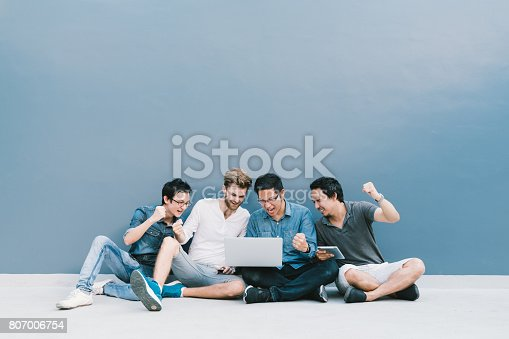 istock Multiethnic group 4 men celebrate together using laptop computer, sit by blue wall with copy space. College student lifestyle, information technology gadget, education, social network, or success concept 807006754