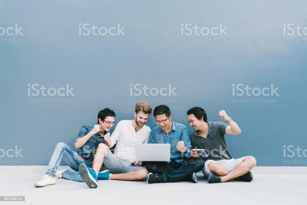 Homens do grupo multiétnico 4 celebrar juntos usando o computador portátil, sente-se por parede azul com espaço de cópia. Estilo de vida de estudante universitário, aparelho de tecnologia de informação, educação, rede social ou conceito de sucesso - foto de acervo