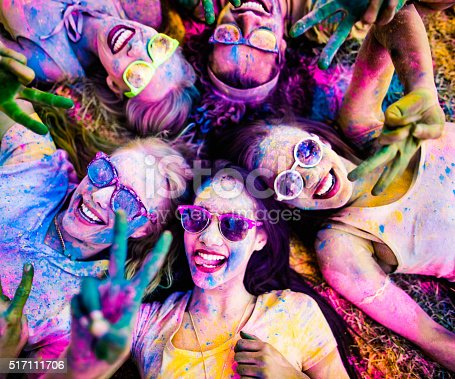 Multi-Ethnic group covered in Holi powder lay in grass laughing and looking up and gesturing peace sign to the camera in a park at a Holi festival in the summer