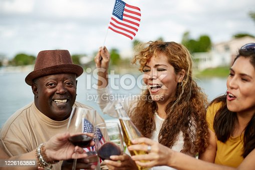 Mature Hispanic women and senior African-American man waving US flags and enjoying celebratory toast in honor of Independence Day.
