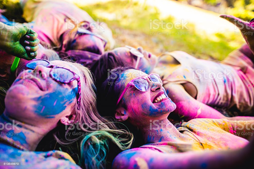 Multi-Ethnic Group Covered in Holi Powder in Park stock photo