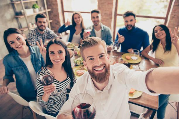 Grupo multiétnico. Bonitão barbudo está fazendo selfie com seus amigos na festa na câmera do seu telefone. Todos estão sorrindo e e desfrutando de sua companhia, se divertindo - foto de acervo